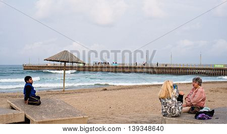 DURBAN SOUTH AFRICA - AUGUST 17 2015: People sitting near the pier at North Beach on the Golden Mile promenade.