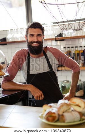 Waiter leaning against counter in the cafe
