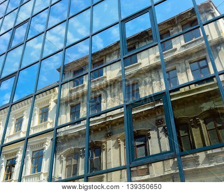 reflection of the old house and the sky with clouds in the windows of the new