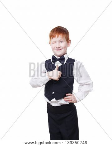 Little cute redhead boy in vest with bow tie shows thumb up and wink. Portrait of well-dressed child in bow tie, approval, , satisfaction gesture. Kid isolated on white background