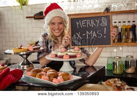 Woman holding blackboard with merry christmas in the cafe