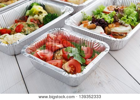 Healthy food delivery and diet concept. Take away of fitness meal. Weight loss nutrition in foil boxes. Roasted eggplant with guacamole and fresh tomatoes at white wood
