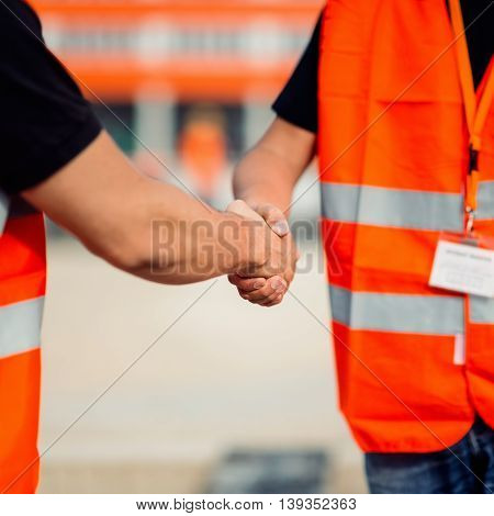 Construction workers handshaking after meeting on construction site