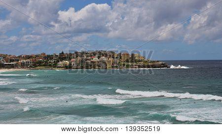 Coastal scene at Bondi Beach. Waves and houses at the shore.