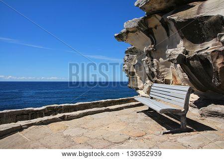 Nature background. Scene near Bondi Beach Sydney. Azure blue Pacific bench and beautiful shaped rock.
