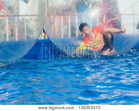 Young Asian Boy Playing Inside A Floating Water Walking Ball