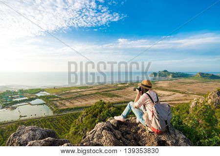 Asian Hipster Girl Sitting On The Peak Of Mountain With Camera.