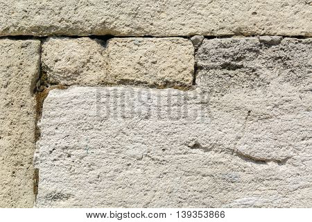 gray wall of sandstone blocks of rectangular shape with uneven edges