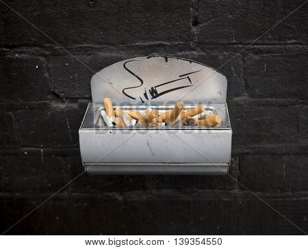 ashtray at a wall with lots of cigarette butts
