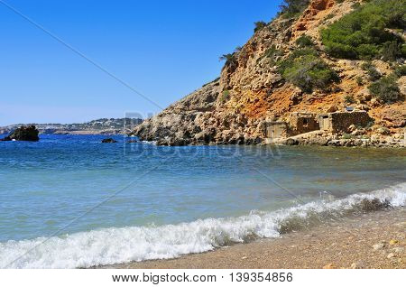 a view of a lonely cove in Ibiza Island, Spain, with some traditional fishermen shelters