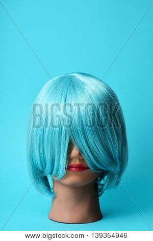 a mannequin head with a blue hair wig on a blue background