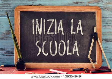 a chalkboard with the text inizia la scuola, back to school in italian, and some old stationery, such as a pen nib in an ink bottle, a compass or some pencil crayons, against a blue wooden background