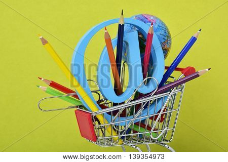 a three-dimensional at sign, a pile of colored pencils and an at sign in a shopping cart, depicting the concepts of the e-learning, the e-teaching, the distance education or the educational technology