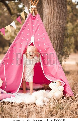 Laughing kid girl 1-2 year old playing in wigwam outdoors. Looking at camera. Childhood.