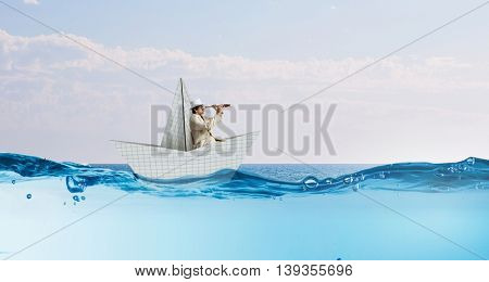 Businessman floating in paper ship . Mixed media