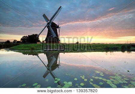 sunrise on Dutch farmland with windmill reflected in river