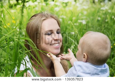 Happy mother with her son in a meadow talking