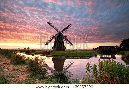 spectacular sunrise over farmland with windmill Netherlands