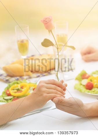 Dating, lunch or dinner concept. Closeup toned image of man and woman holding hands while having lunch or dinner in restaurant or cafe by sea.