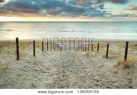 sand path to the North sea at sunset Holland