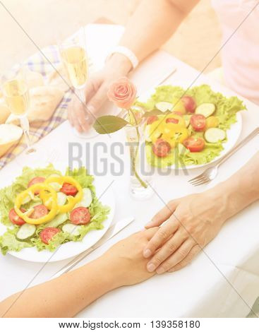 Toned picture of beautiful couple holding hands and having lunch or dinner in restaurant or cafe. Man and woman resting spending free time all together on sunny day.