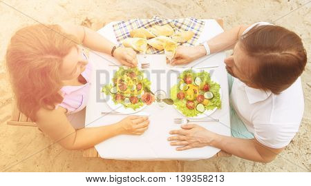 Top view image of mature couple having date in restaurant or cafe. Beautiful people sitting at table and having lunch or dinner. People communicating and happy smiling.