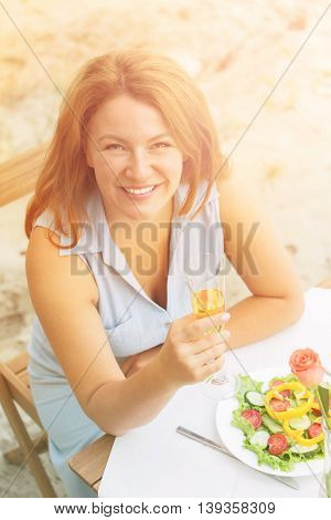 Closeup toned picture of happy smiling red-haired woman in blue dress looking at camera and holding glass of white wine.