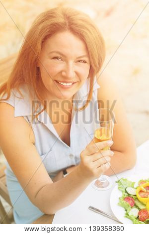 Closeup toned image of beautiful woman holding glass of white wine and smiling to camera. Red-haired woman in blue dress sitting in restaurant or cafe.