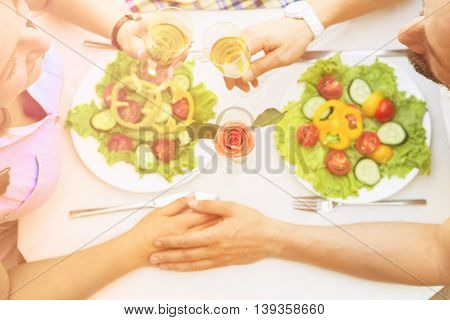 Man and woman resting spending free time all together on sunny day. Toned picture of beautiful couple holding hands and having lunch or dinner in restaurant or cafe.