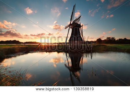 Dutch windmill by lake at sun down Netherlands