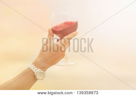 Toned picture of glass with old red wine in sommelier's hand. Red wine is tasted by sommelier isolated on blue sky background.