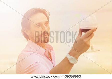Toned picture of sommelier analyzing a glass of red wine isolated on blue sky background. Black-haired mature man happy looking at glass.