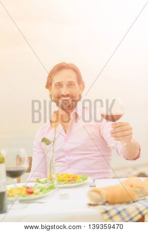 Toned picture of handsome mature man smiling for the camera while holding glass of red wine in his hand. Handsome man in pink shirt resting in restaurant or cafe.