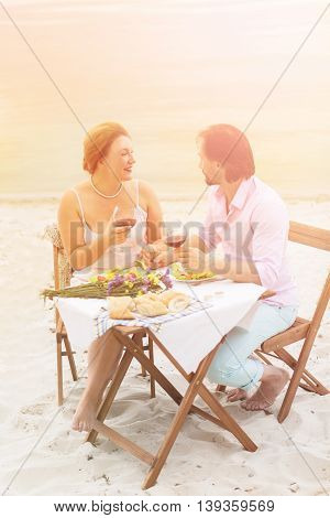 Toned picture of man and woman enjoying sea view in restaurant or cafe at beach. Happy couple having lunch or dinner with red wine isolated on sea.