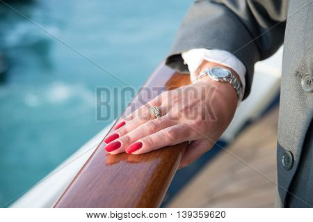 Female hand and wrist-watch with red manicure and golden ring on finger with diamonds near water