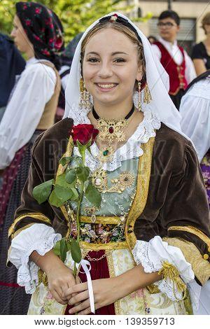 SELARGIUS, ITALY - September 13, 2015: Former marriage Selargino - Sardinia - portrait of a beautiful smiling girl in Sardinian costume holding a rose in hand