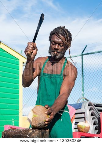 Nassau Bahamas - January 07 2016: african american muscular man break big fresh raw coconut with sharp machete smoking cigar outdoor in green apron