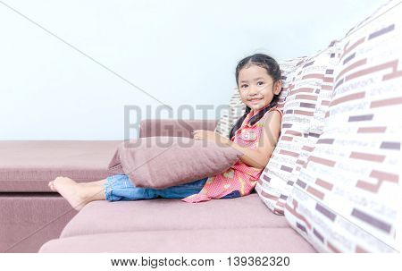 Portrait of cute asian Thai little girl playing mobile phone at home with copy space