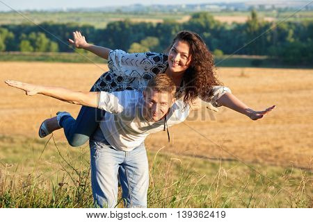 happy couple having fun on outdoor, girl riding on man back and fly - romantic travel and people concept, summer landscape with wheaten field