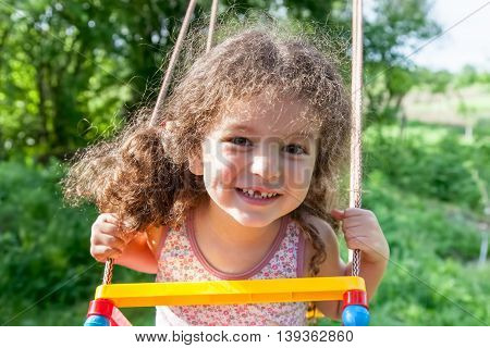 Portrait of cheerful baby girl on swing closeup outdoors
