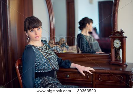 Portrait of young beautiful fashionable woman in the interior near the mirror