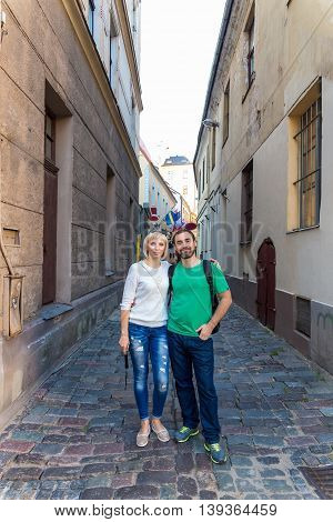 Happy couple of tourists taking selfie in old city of Riga Latvia