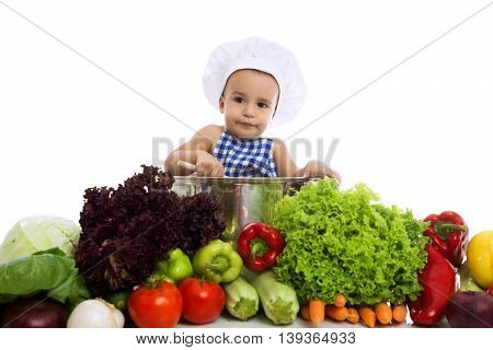 Little Boy In Chef's Hat Sitting In Pot With Vegetables