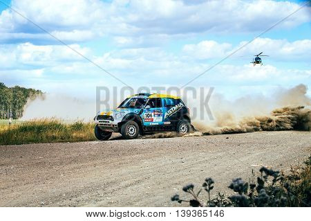Filimonovo Russia - July 11 2016: rally car driving on a dusty road above him flies a helicopter during Silk way rally