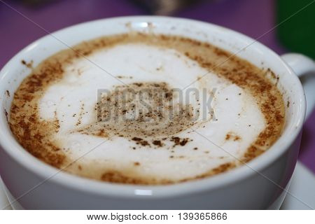 Freshly brewed cappuccino, with a decorative pattern on the foam heart