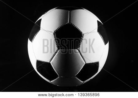 Black and white soccer ball on black background.