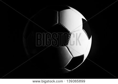 Black and white soccer ball in a dark blackground.