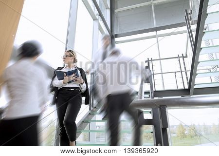 Busy office building corridor three business people in a motion focus on woman standing and taking notes