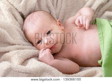 Smiling Newborn Baby Lying On Blanket
