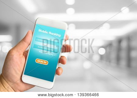 Woman hand holding smartphone against white grey bokeh abstract background mobile banking concept